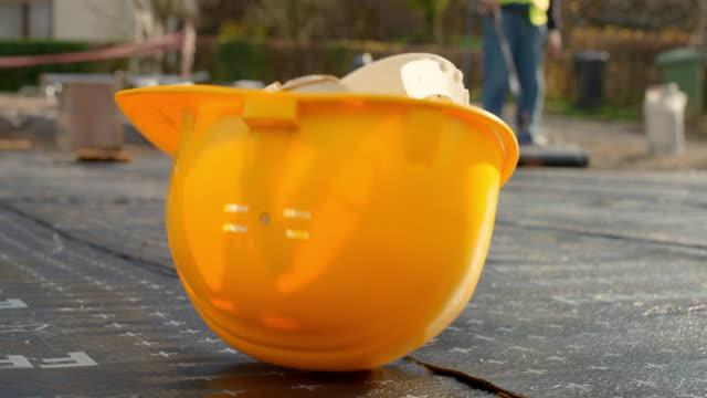 vídeos y material grabado en eventos de stock de casco de construcción amarillo cayendo sobre el suelo en el sitio de construcción - material de construcción