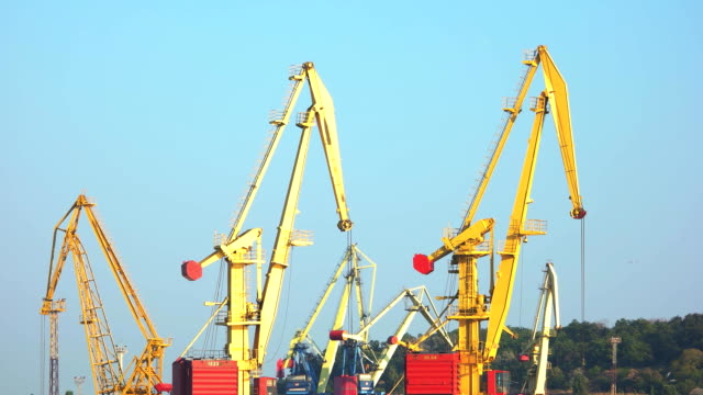 Yellow cranes for lifting up cargo. Yellow cranes for lifting up cargo. Blue sky background. international match stock videos & royalty-free footage