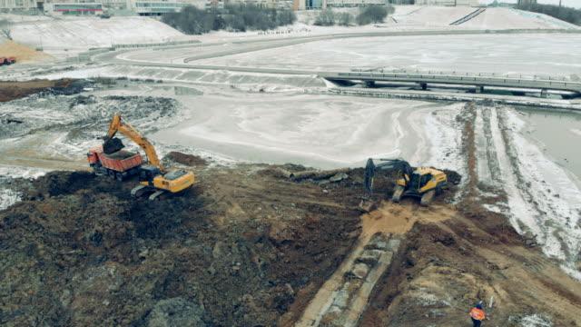 gelber bagger arbeitet in einem steinbruch, gräbt erde. - eimer stock-videos und b-roll-filmmaterial