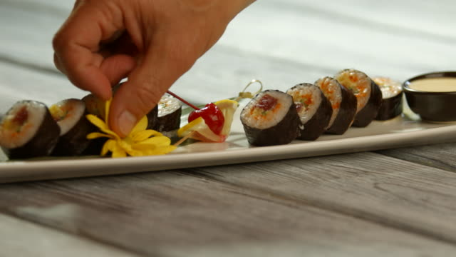 Yellow flowers on sushi plate. video