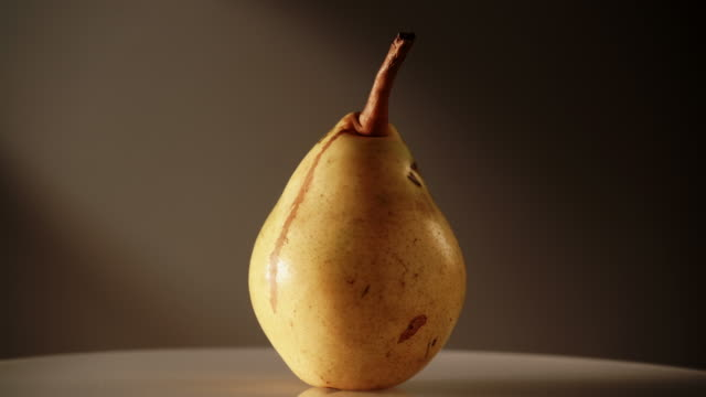 黄色い新鮮な熟した梨が暗闇で回転する ビデオ