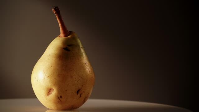 Yellow fresh ripe pear rotating on dark