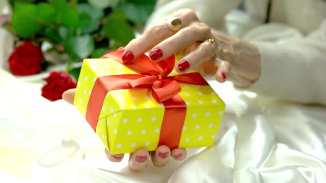 yellow gift box in female hands. - nastro per capelli video stock e b–roll
