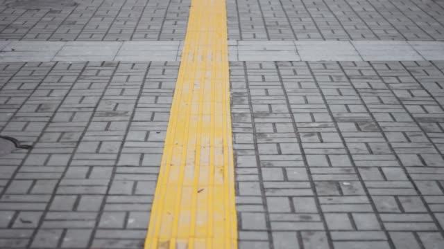 vídeos y material grabado en eventos de stock de línea amarilla para ciegos en adoques grises. espacio perspective.copy - descripción física