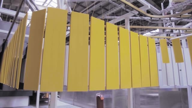 Yellow metal panels move on an overhead conveyor. - vídeo