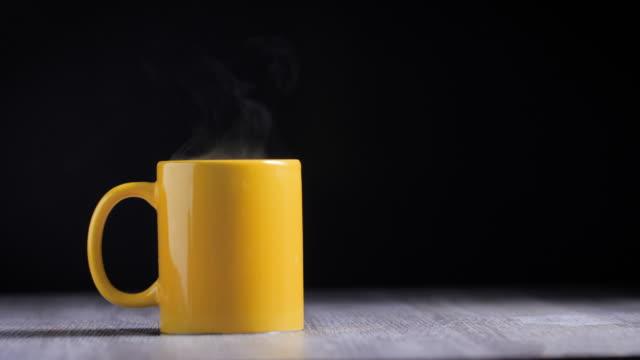 la tazza gialla contiene il caffè caldo con fumo su uno sfondo nero - calore concetto video stock e b–roll