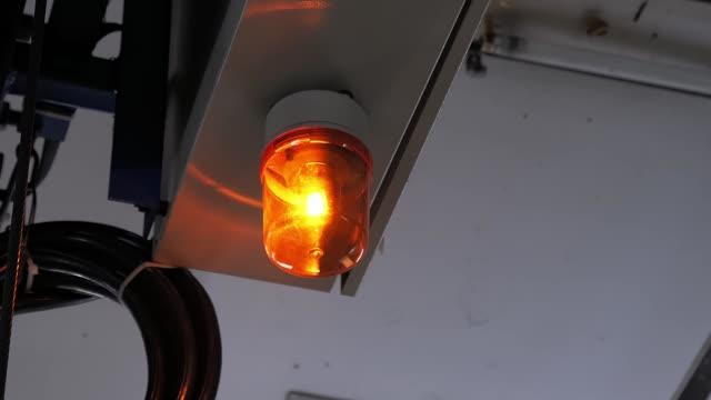 vidéos et rushes de lumière rotative jaune d'avertissement de lumière de sirène orange dans le signe industriel de sûreté de côté - danger