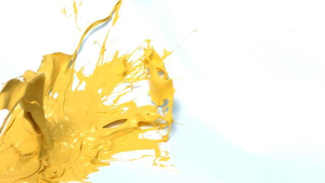 Yellow paint splattering on white background