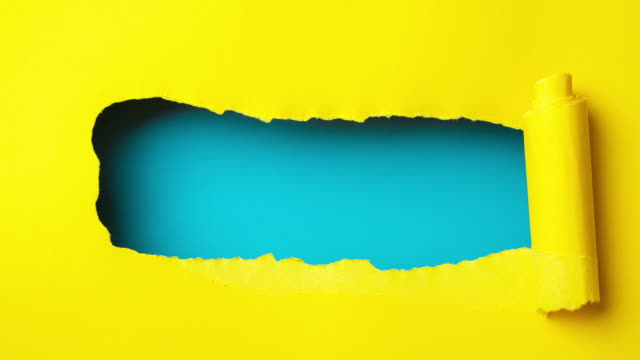 Yellow paper is torn over blue background for message, stop motion, animation.