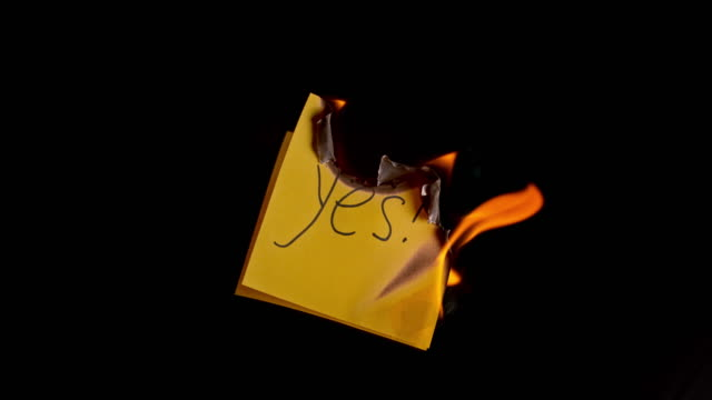 SLO MO LD Yellow paper with inscription 'yes!' burning