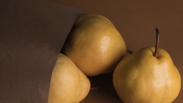 Yellow pear in paper shopping bag over brown background