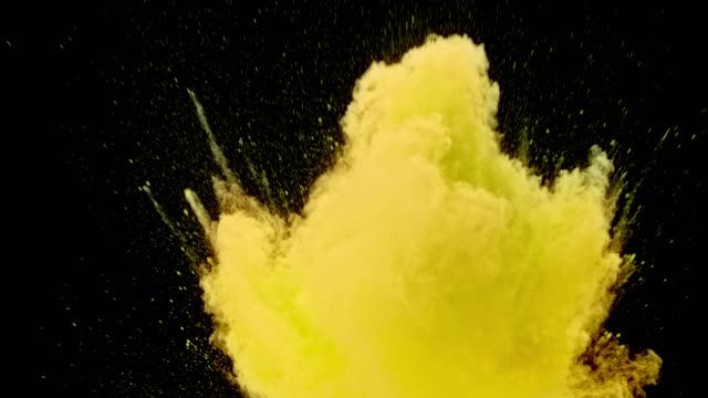 SLO MO Yellow powder dust bursting into the air on black background Slow motion wide locked down shot of a column of bright yellow colored powder bursting into the air upright on black background causing a yellow cloud. Shot in Slovenia. yellow stock videos & royalty-free footage