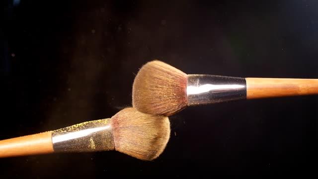 vidéos et rushes de explosion de poudre jaune avec 2 brosses de beauté - pinceau à maquillage