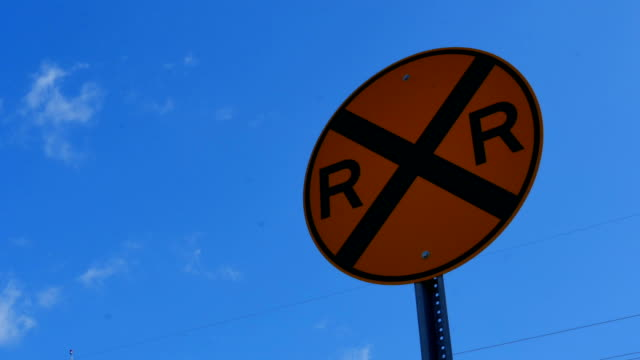 Yellow railroad sign against time lapse sky video