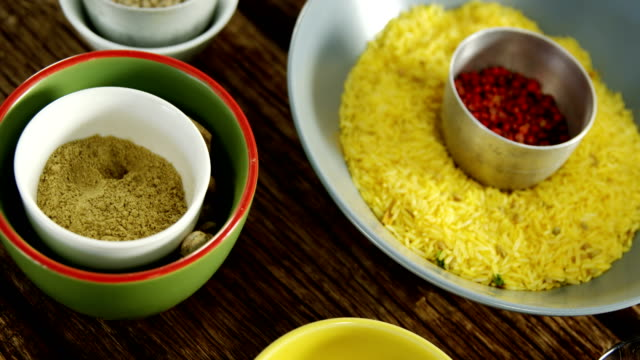 Yellow rice with various spice on wooden table 4k video