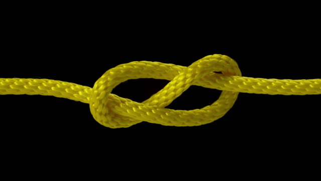 SLO MO LD Yellow rope being pulled into a tight knot