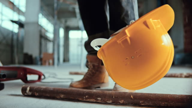 SLO MO Yellow safety helmet being falling on the ground at the construction site Slow motion locked down shot of a yellow safety helmet falling on the ground at the construction site and legs of a construction worker seen in the background. Shot in Slovenia. work helmet stock videos & royalty-free footage