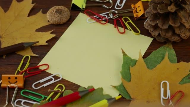 foglio di carta giallo con foglie d'acero caduto gialle e forniture per ufficio - educazione primaria video stock e b–roll