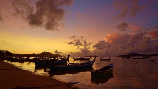 balıkçı teknelerinin üzerinde sarı gökyüzü parlıyordu - andaman denizi stok videoları ve detay görüntü çekimi