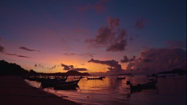 rawai plajının üzerinde sarı gökyüzü parlıyordu - andaman denizi stok videoları ve detay görüntü çekimi