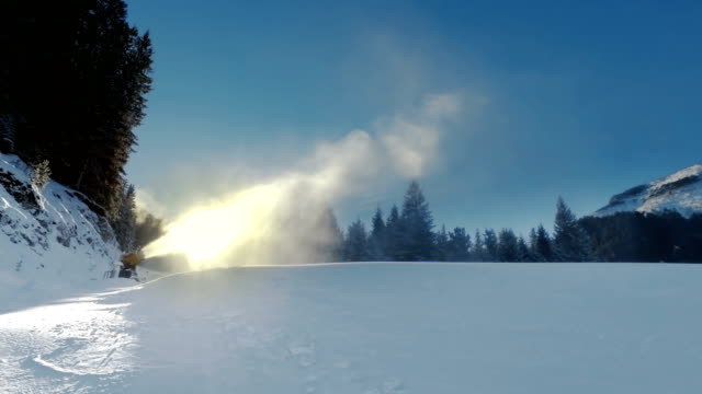 Yellow snow cannon stands on a snowy mountain in the winter against sun and works by producing a column of snow on the background of beautiful mountains, snow-covered pine trees, and the ski slope video