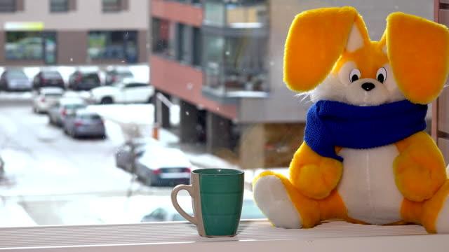 stockvideo's en b-roll-footage met gele speelgoed bunny met thee kop zitten door raam in de winter. sneeuwvlokken vallen. - camelia white