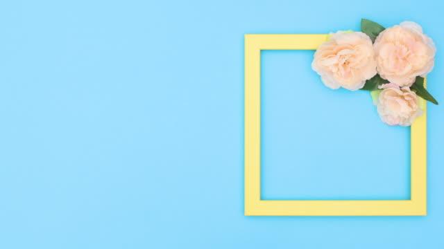 vídeos de stock e filmes b-roll de yellow transparent frame for text with flowers appear on blue theme. stop motion - padrão repetido