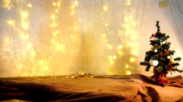 yellow twinkling  garlands and christmas tre - ghirlanda decorazione video stock e b–roll