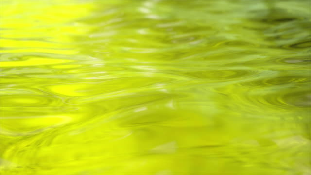 Yellow wave moving liquid surface. Water ripples. Seamless loop 3d render