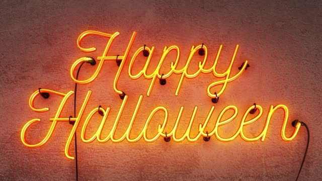 Yellow/Orange neon sign saying Happy Halloween on a grey concrete wall background, the footage starts with the sign off, then it stays on for 30 seconds them flashes on and off for another 30 seconds.