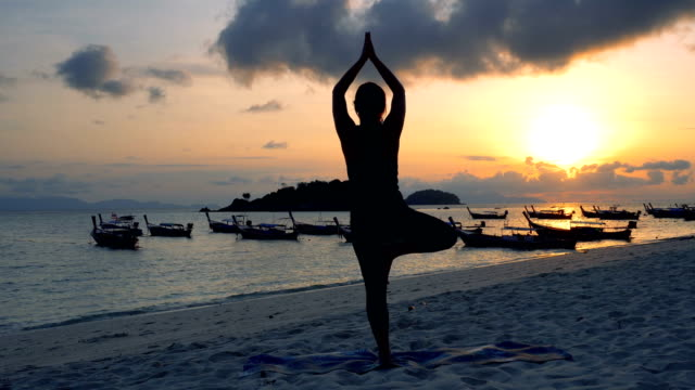 Yoga at sunrise beach. Tree pose Woman practicing yoga, tree . Beach sunrise. Moody sky and boats' silhouettes physical position stock videos & royalty-free footage