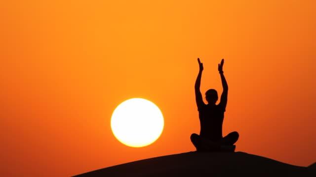 yoga al tramonto seduti - gambe incrociate video stock e b–roll
