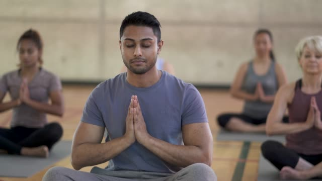 Yoga Class Prayer Pose A group of adults are doing yoga in a group fitness class. They are content and appear to be in a zen like state and are doing a prayer pose zen like stock videos & royalty-free footage