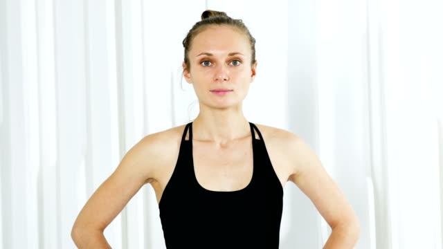 fille d'yoga en robe noire est debout dans un studio blanc - Vidéo