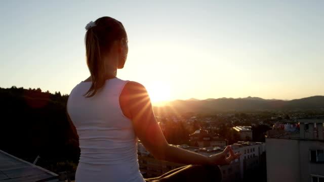 蓮のポーズで瞑想、屋上の端に座っているクローズ アップのヨガ女の子 - 屋根点の映像素材/bロール