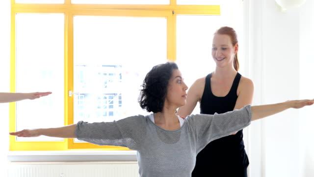 Yoga instructor assisting women at health club video