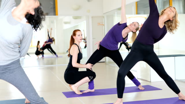 Yoga instructor guiding women at health club video