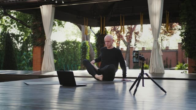 Yoga instructor in black sportswear is sitting in lotus position and looking at laptop. Shooting himself on video by smartphone on tripod at courtyard