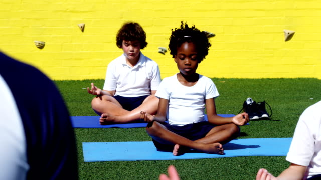 Yoga instructor instructing children in performing yoga Yoga instructor instructing children in performing yoga in campus mindfulness stock videos & royalty-free footage
