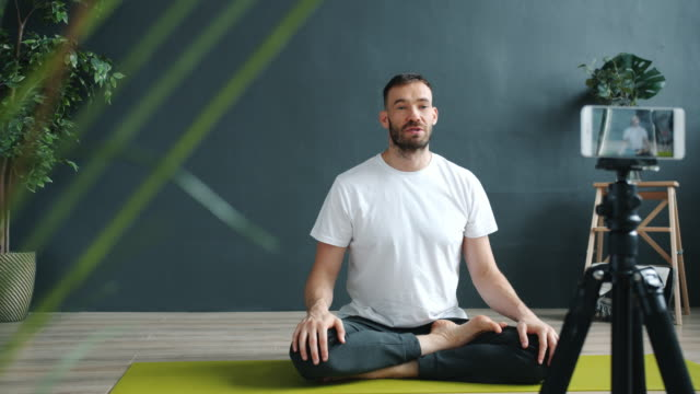 Yoga instructor teaching online recording tutorial in studio with smartphone video