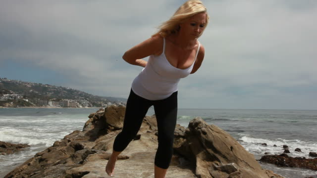 yoga on rocky beach - cleavage stock videos and b-roll footage