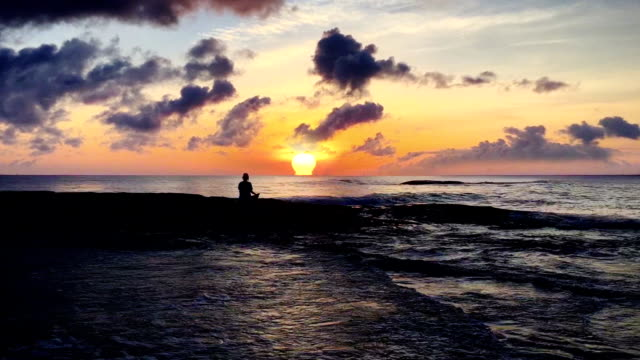 Yoga on the beach. Woman meditating in lotus pose. Sunset video