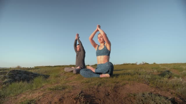 yoga religion, sports pair together meditating in lotus position on meadow on background of sky yoga religion, sports pair together meditating in lotus position on meadow on background of blue sky pigtails stock videos & royalty-free footage
