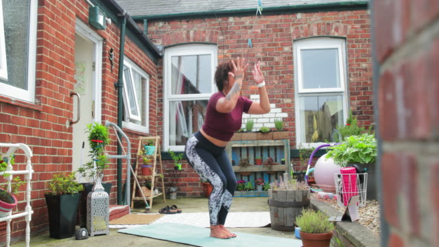 Yoga Stretches A mixed-race mid-adult female yoga instructor performing a Chair Pose with arms forward, she is in her back yard, during the Corona Virus Pandemic. mental wellbeing stock videos & royalty-free footage