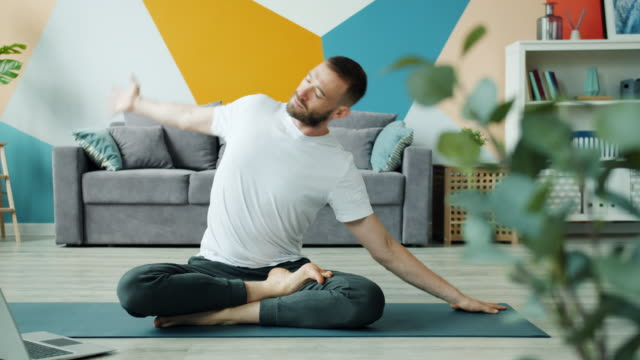 yoga student learning asanas online using laptop at home exercising on mat - posizione corretta video stock e b–roll
