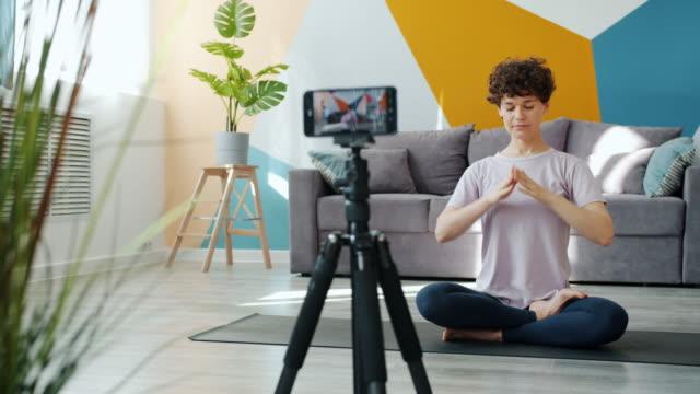 yoga teacher recoding video doing asanas meditating talking in modern apartment - influencer стоковые видео и кадры b-roll