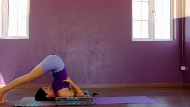 Yoga teacher using blankets, belt and mat to prepare back bend pose on purple studio Young woman takes legs back, up and finishes on setu bandha sarvangasana. Energizing, restorative concepts prop stock videos & royalty-free footage