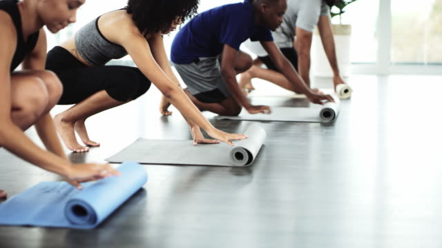 Yoga time 4k video footage of a group of young people rolling out their yoga mats inside a yoga studio styles stock videos & royalty-free footage