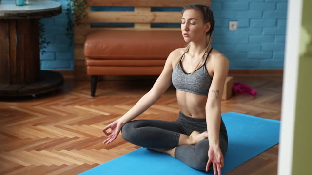 Yoga Woman exercising yoga at home lotus position stock videos & royalty-free footage