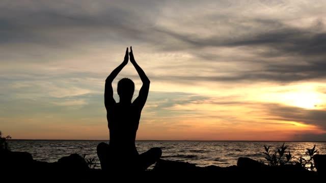 Femme de yoga en posture de lotus sur la plage au coucher du soleil - Vidéo